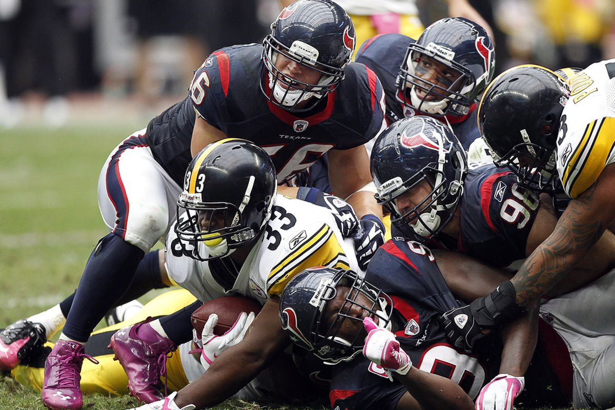 HOUSTON - OCTOBER 02:  Running back Isaac Redman #33 of the Pittsburgh Steelers is tackled by Brian Cushing #56 and Connor Barwin #98 of the Houston Texans at Reliant Stadium on October 2, 2011 in Houston, Texas.  (Photo by Bob Levey/Getty Images)