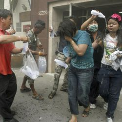 Tourists escape from a hotel fire after a blast in Songkhla province, southern Thailand, on Saturday.