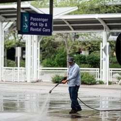 A man power washes the sidewalk outside Salt Lake City International Airport on Thursday, April 30, 2020. Like airports all over the world, Salt Lake's airport has seen air traffic plummet due to the COVID-19 pandemic.