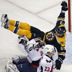 Boston Bruins left wing Benoit Pouliot (67) flies through the air as he collides with Washington Capitals goalie Braden Holtby (70) on his game-tying goal during the third period of Game 2 of an NHL hockey Stanley Cup first-round playoff series in Boston, Saturday, April 14, 2012.