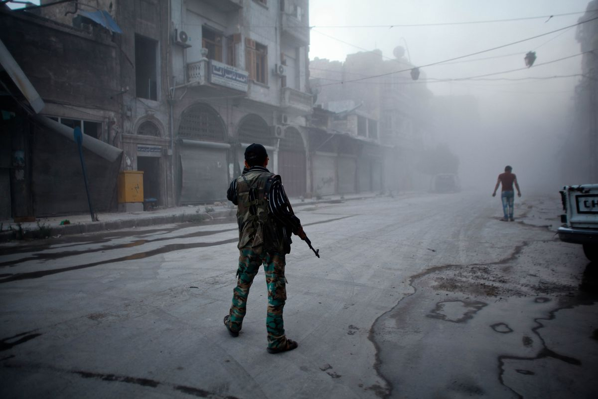 A Syrian rebel stands in the street in Aleppo.