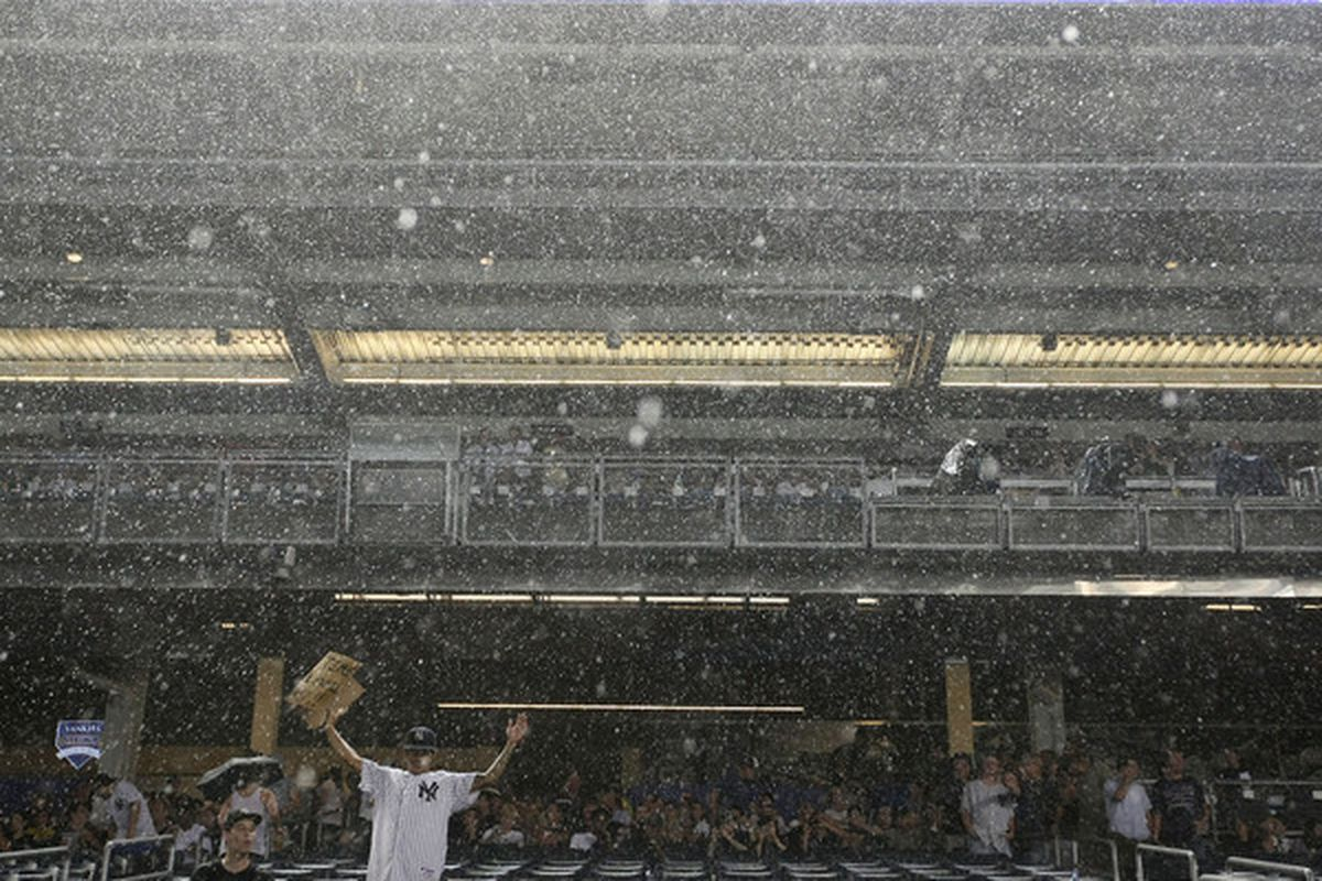 NEW YORK - JULY 23: Fans stand during a rain delay in the game between the New York Yankees and the Kansas City Royals on July 23 2010 at Yankee Stadium in the Bronx borough of New York City.  (Photo by Al Bello/Getty Images)