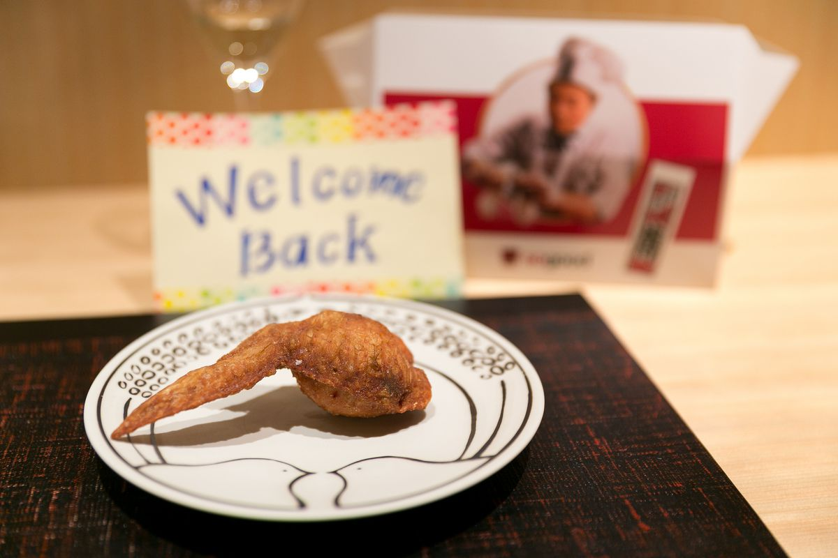 """A chicken wing on a plate in front of a sign that reads """"Welcome back."""""""