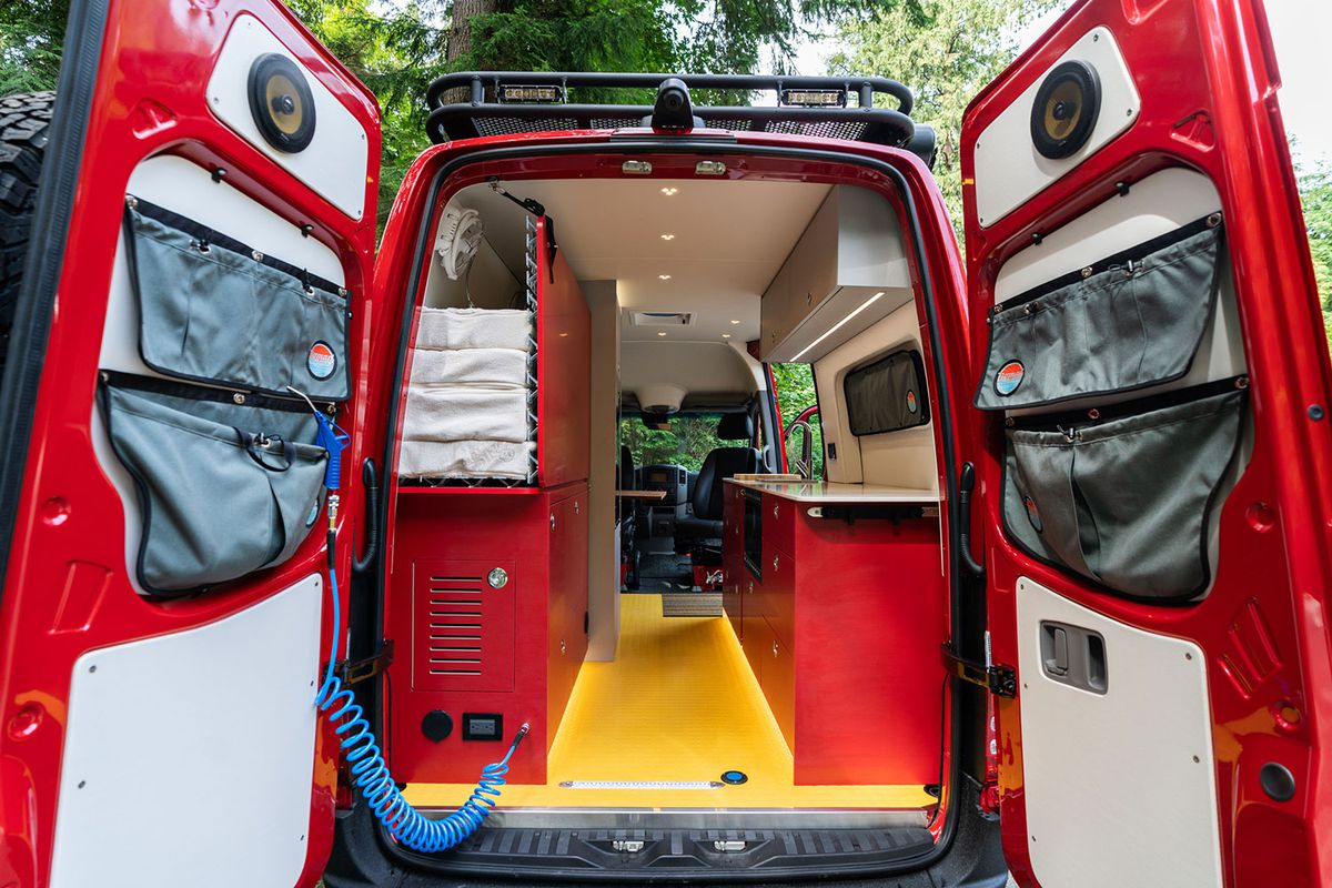 A view of the van's garage area with rear doors open. You see yellow floors, red cabinets, and white trim.