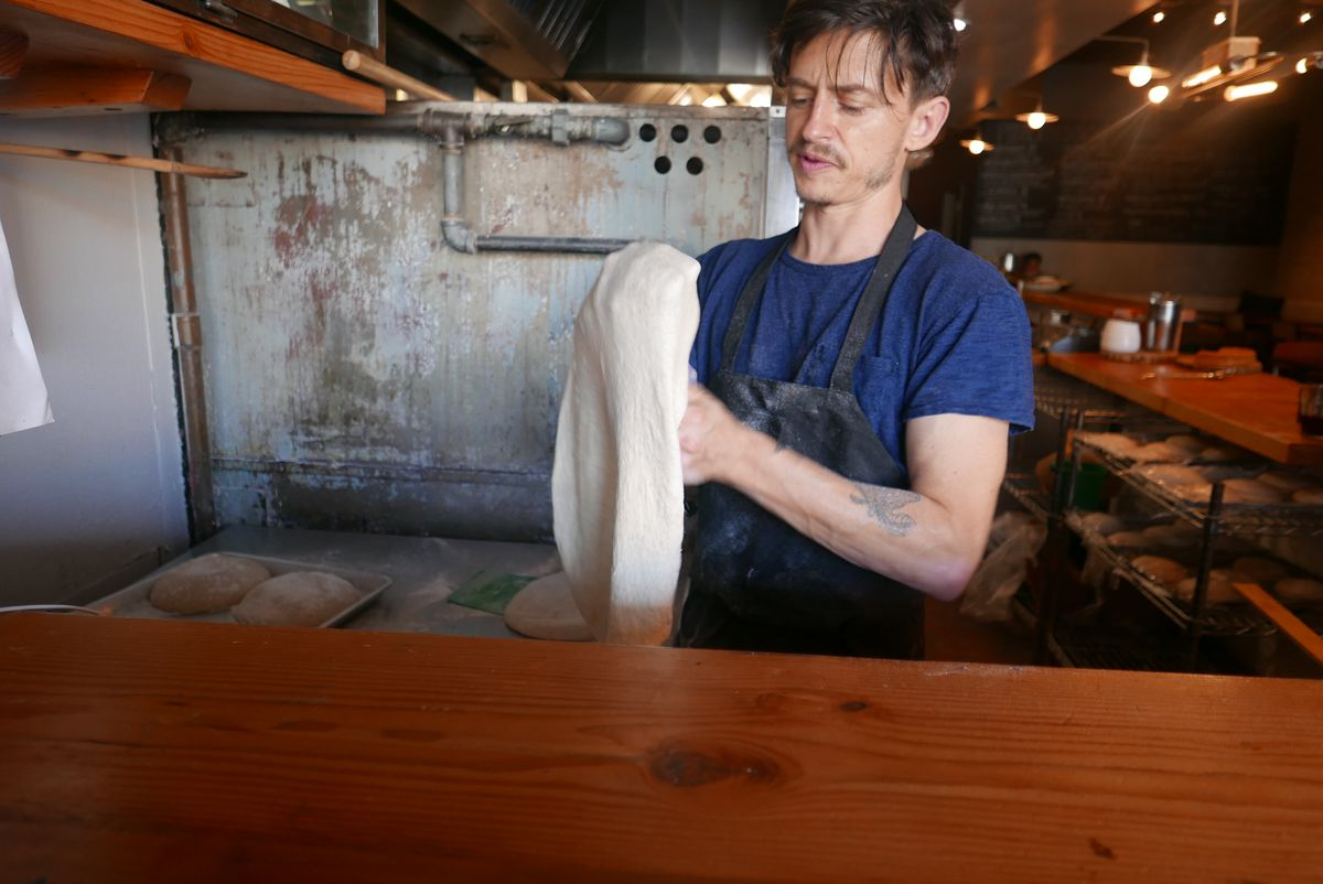 A white man in a blue shirt and apron stretches pizza dough
