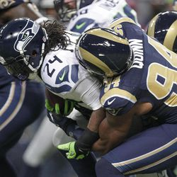 Seattle Seahawks running back Marshawn Lynch (24) is tackled by St. Louis Rams defensive end Robert Quinn during the first half of an NFL football game Sunday, Sept. 30, 2012, in St. Louis.