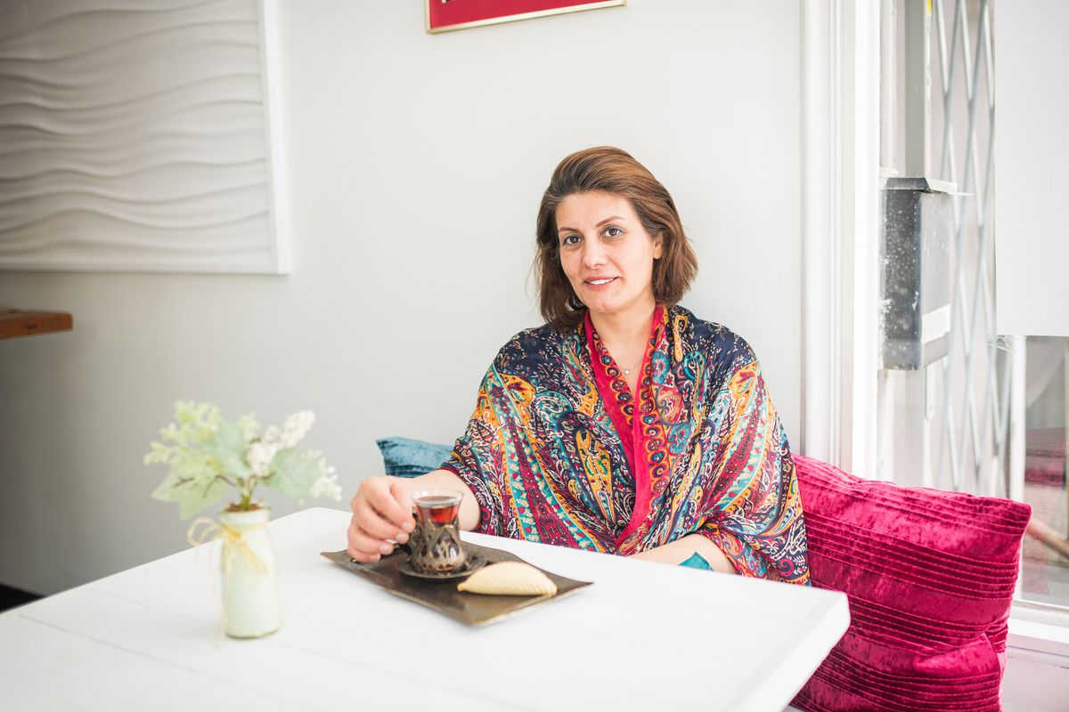 Ilhama Safarova poses for a portrait with a colorful patterned shawl, a cup of tea, and a pastry