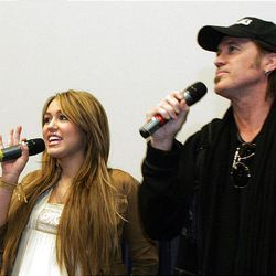 """Miley Cyrus and her father, Billy Ray Cyrus, surprise the audience by appearing Friday at a premiere of her movie """"Hannah Montana,"""" at the Megaplex 20 in South Jordan."""
