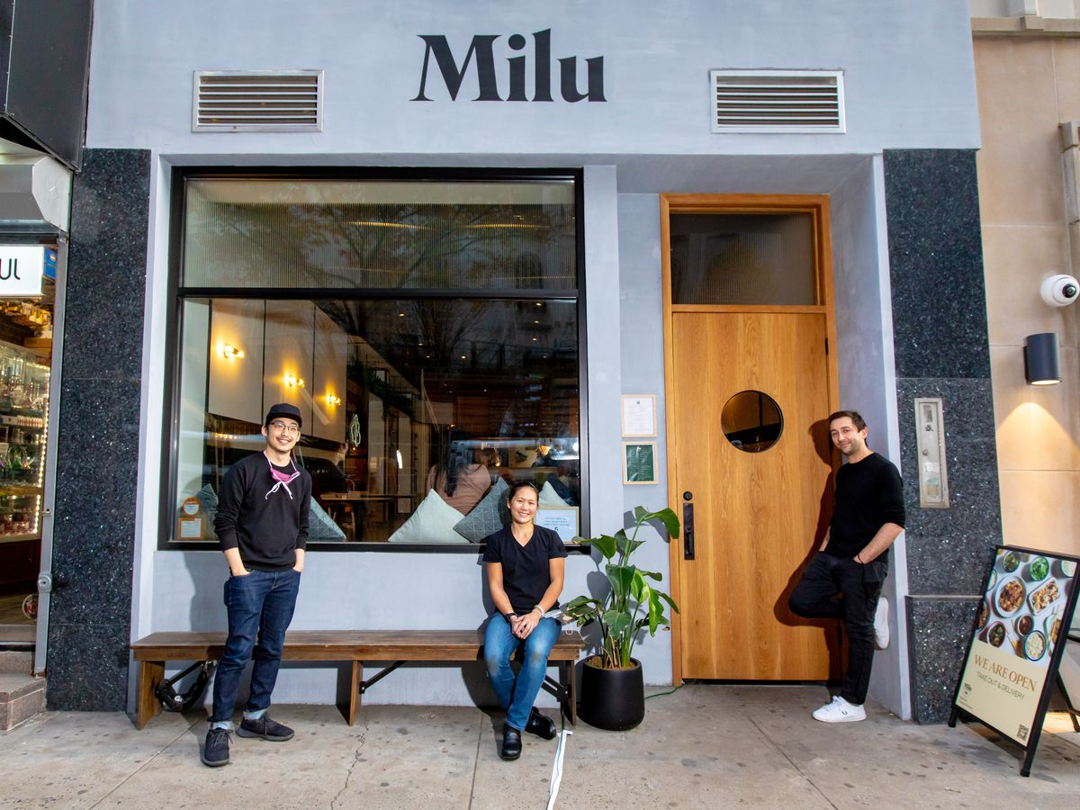 Vincent Chao and Milan Sekluic stand in front of Milu's entrance, while chef Connie Chung sits between them on a wooden bench