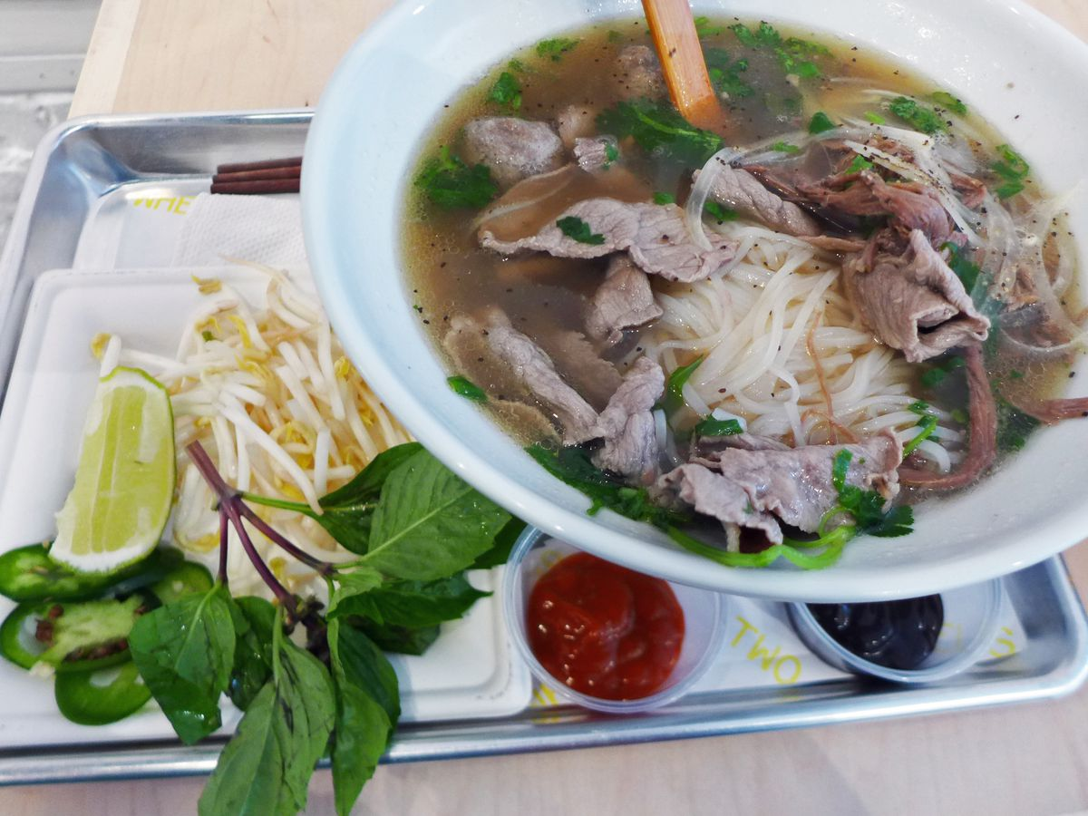 A bowl of brown brothed pho with the rice noodles floating on top and herbs and sprouts on the side.