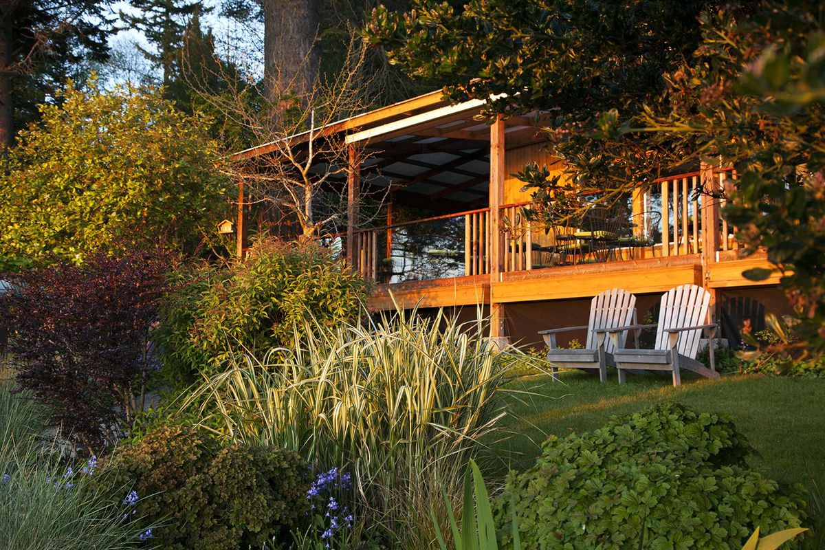 A view of Willows Inn on Lummi Island, with two deck chairs out front and foliage all around