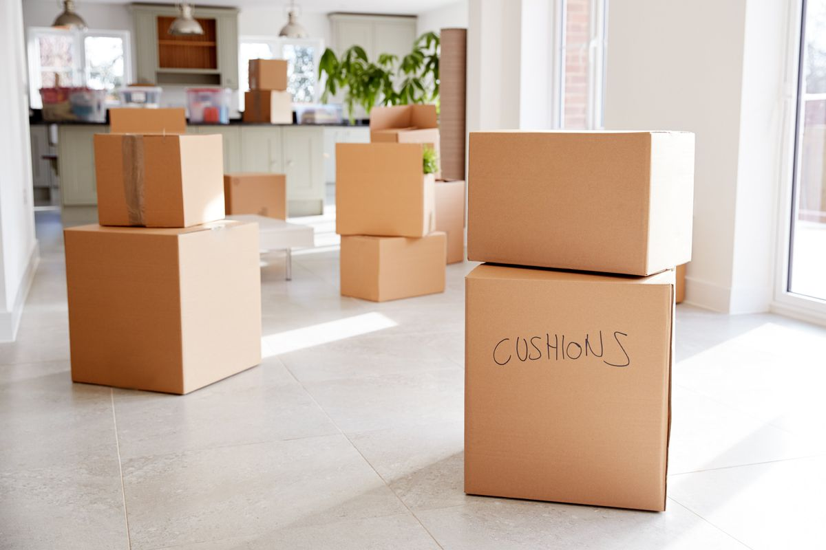 Cardboard moving boxes in a bright, white kitchen area of a home.