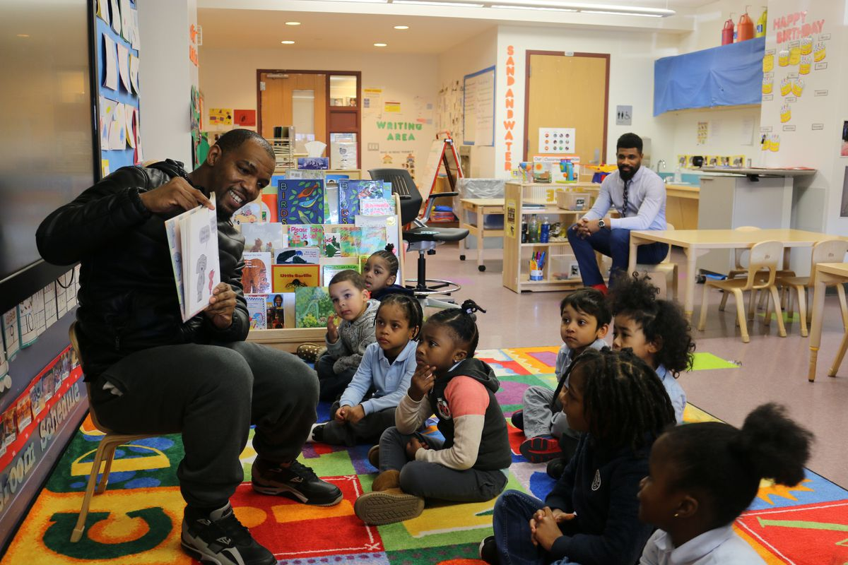 Alphonzo Macon reads to his son's pre-K class at Learning Through Play in the South Bronx. Assistant Principal Anthony Tucker, back right, invites father figures to take an active role in the school to help build students' literacy skills.