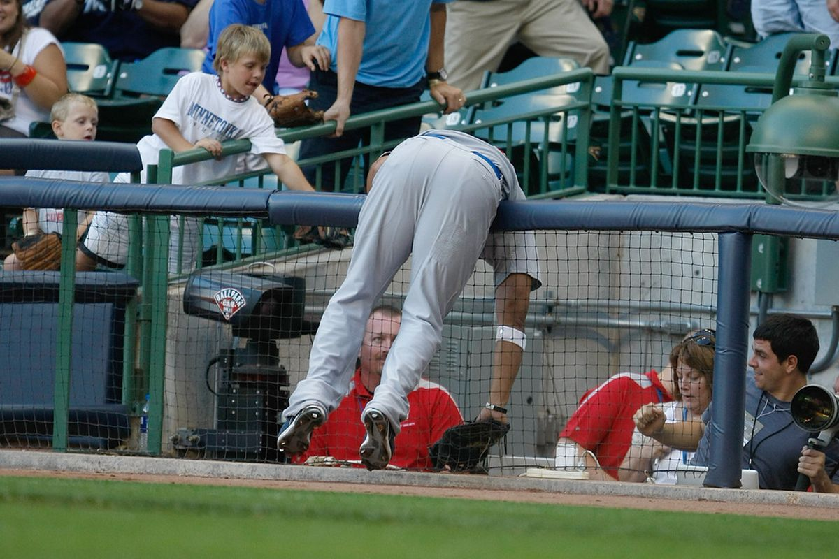 Carlos Pena of the Chicago Cubs dives over the railing in the photo well in an attempt to catch a foul ball during a game against the Milwaukee Brewers at Miller Park in Milwaukee, Wisconsin. (Photo by Scott Boehm/Getty Images)