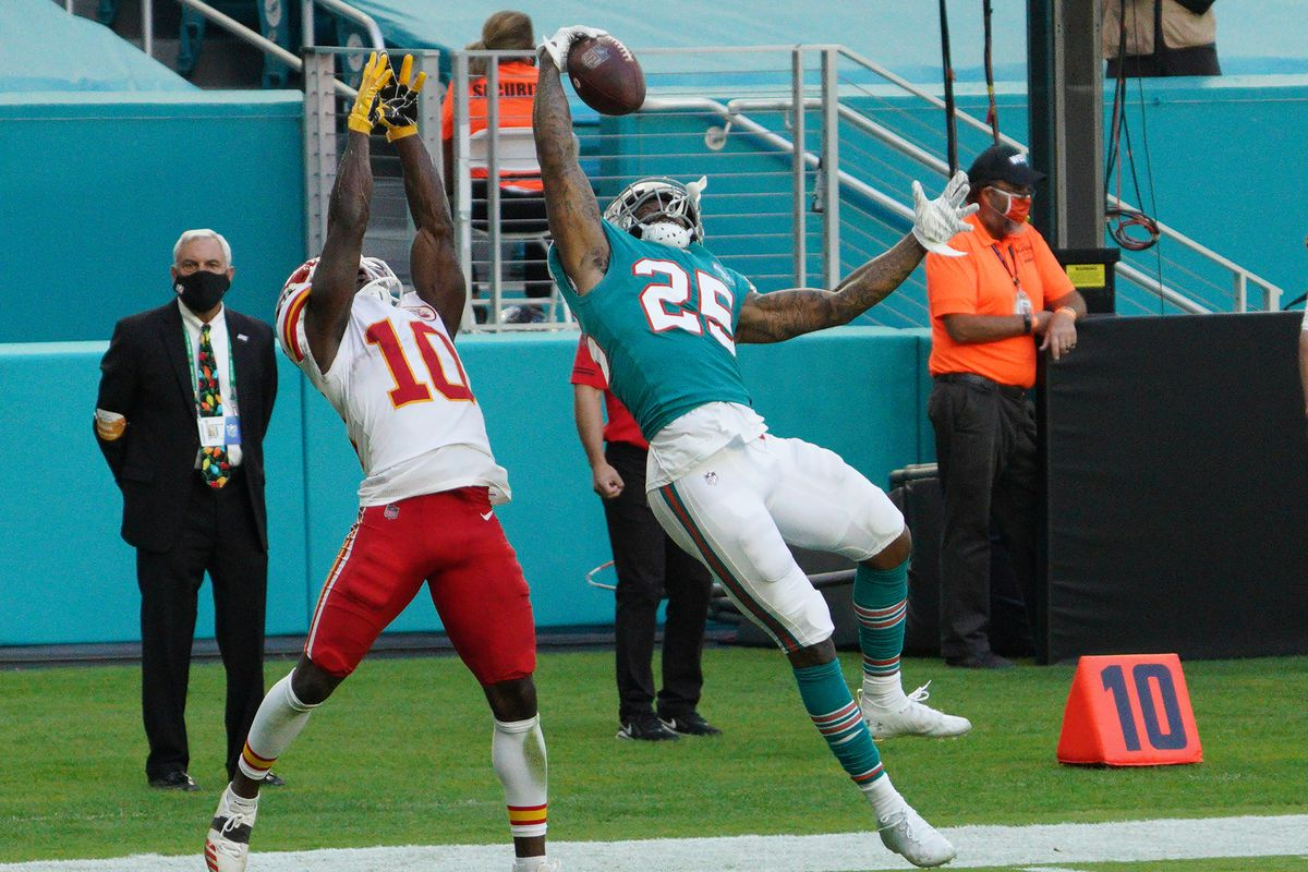 Xavien Howard #25 of the Miami Dolphins intercepts the ball against Tyreek Hill #10 of the Kansas City Chiefs at Hard Rock Stadium on December 13, 2020 in Miami Gardens, Florida.