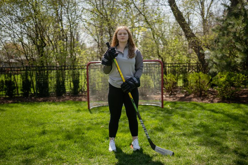 Morgan stands in front of a goal in her backyard with hockey stick in hand.