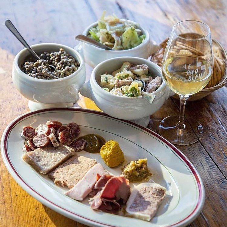 glass of whine with several charcuteries and mustards