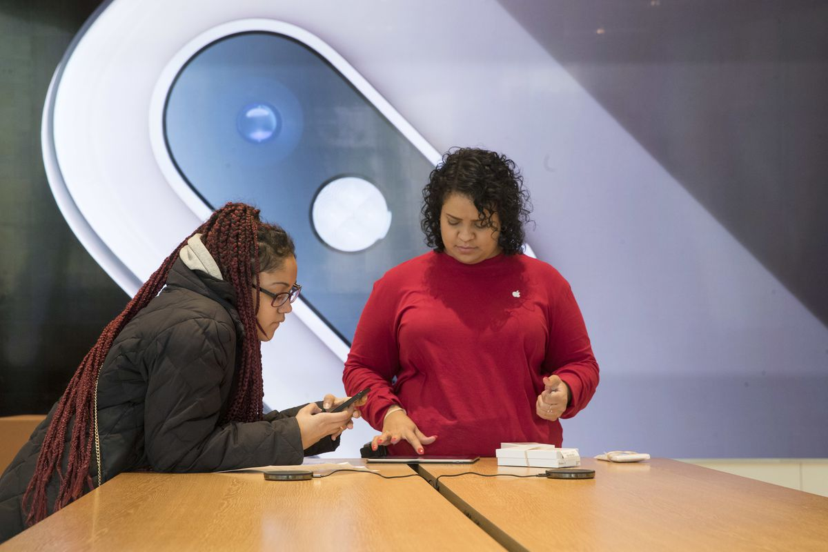 An image of an iPhone is on display in the background as a customer, left, is helped at the Apple store in the Brooklyn borough of New York, Thursday, Jan. 3, 2019.