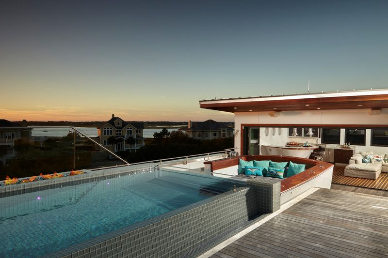A rooftop pool, lounge area, and bar offer sunset views toward other houses and the ocean.