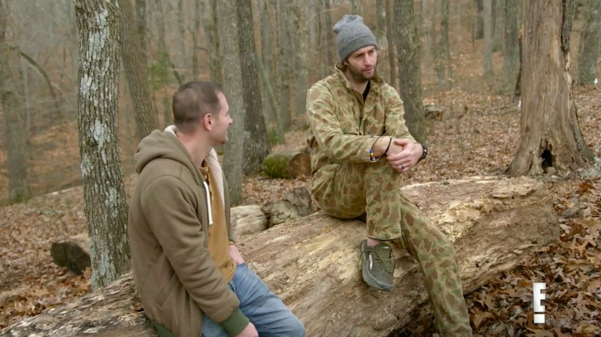 Chuy sitting with Jay Cutler on a log. Jay is wearing camouflage.