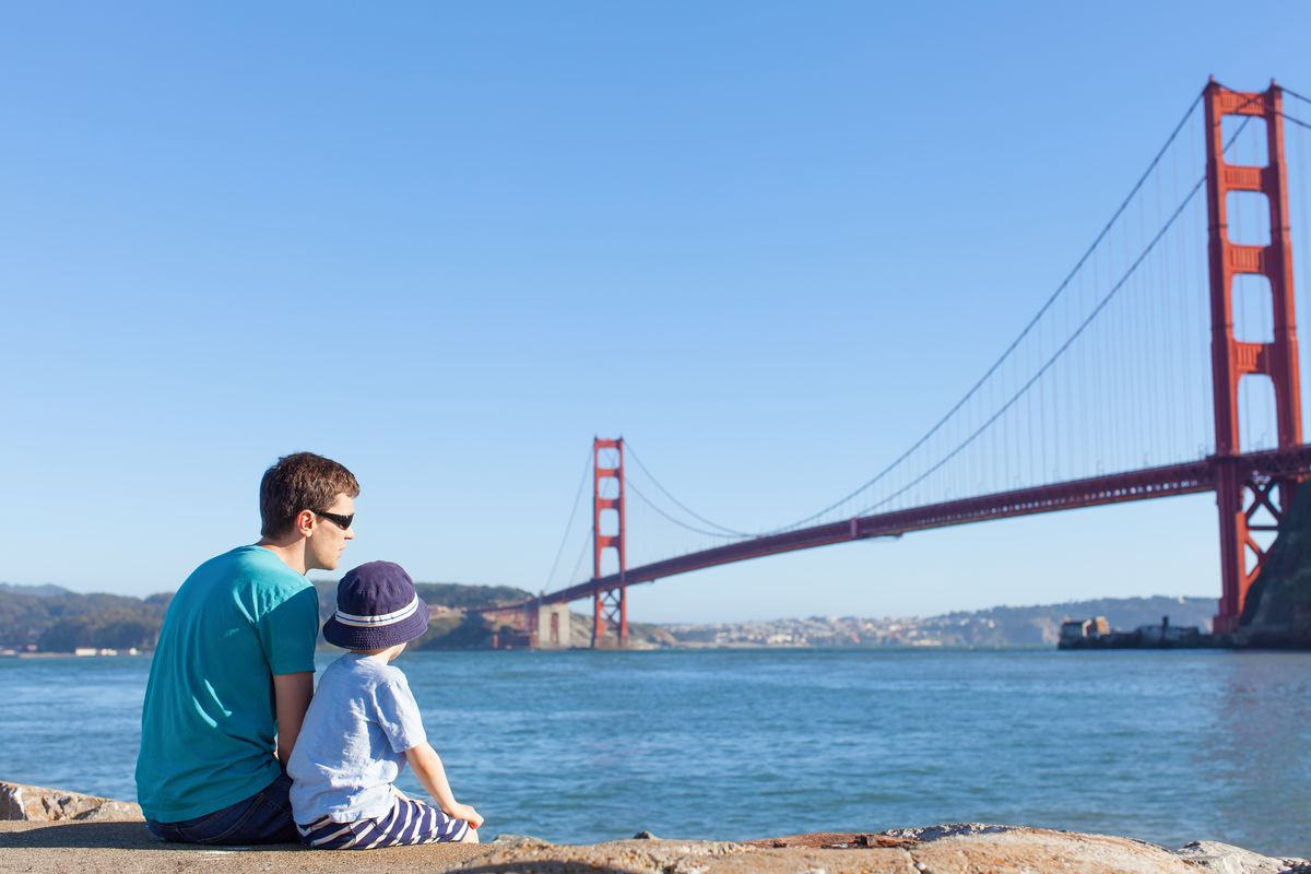A man and a boy sitting and looking at the Golden Gate Bridge.