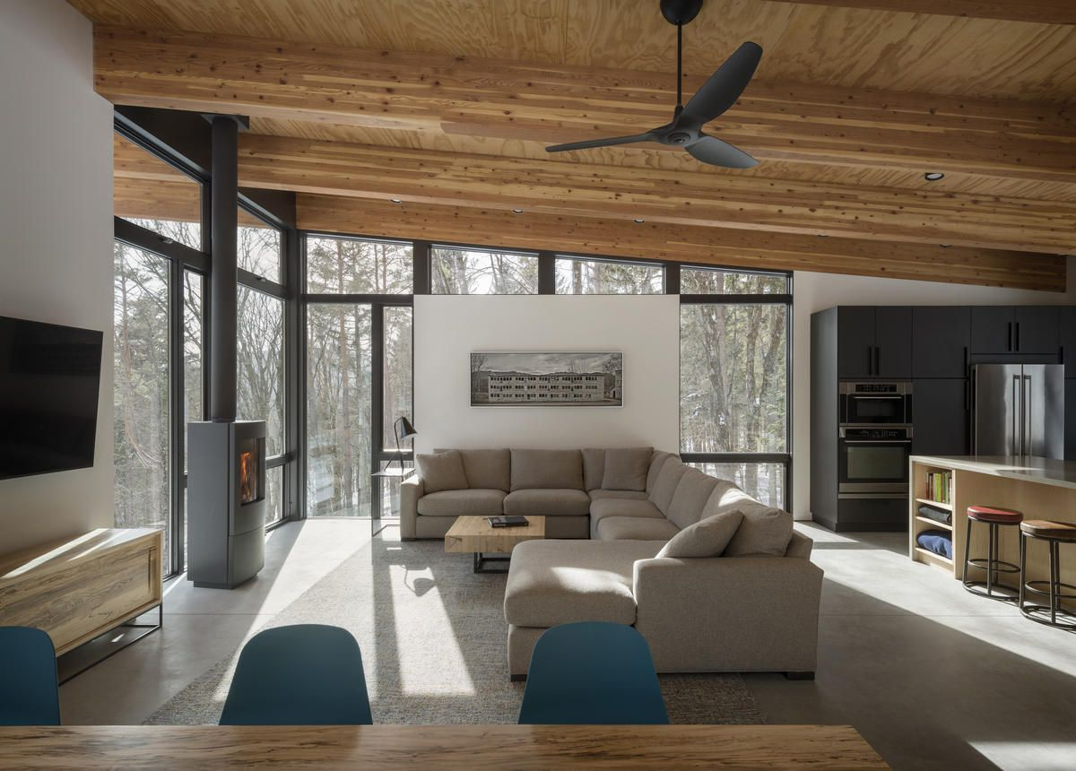 Living room with slanted timber ceiling and open plan layout.