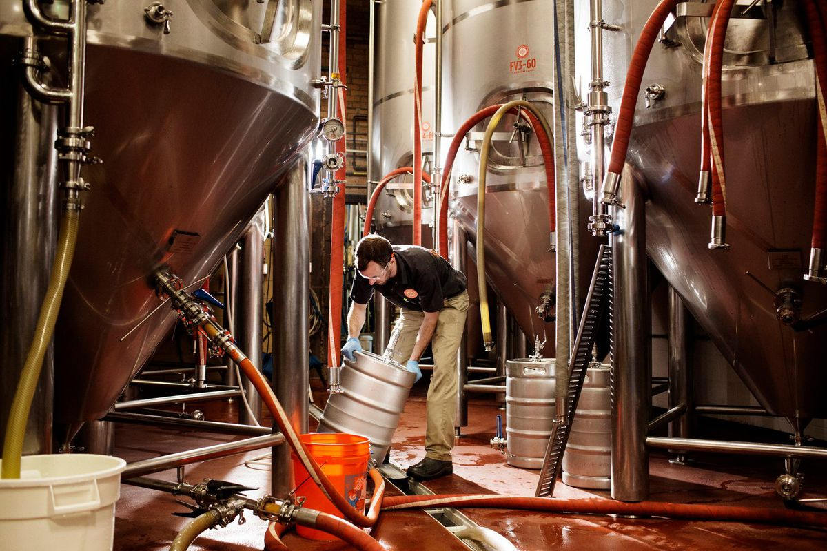A brewer surrounded by tanks lifts a filled keg