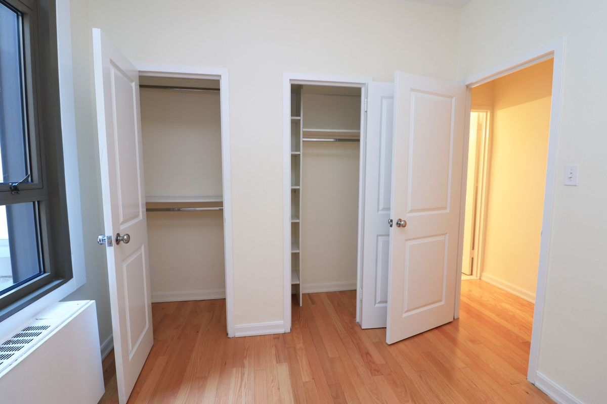A bedroom with hardwood floors, two closets, and beige walls.