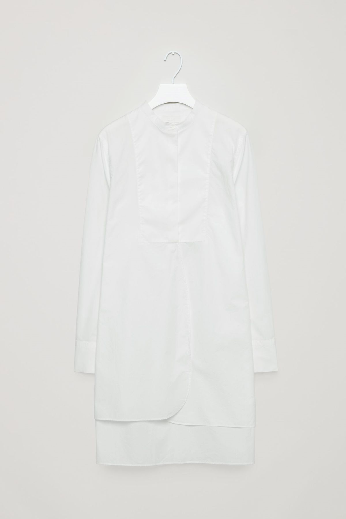 A tunic-length white shirt with a bib front.
