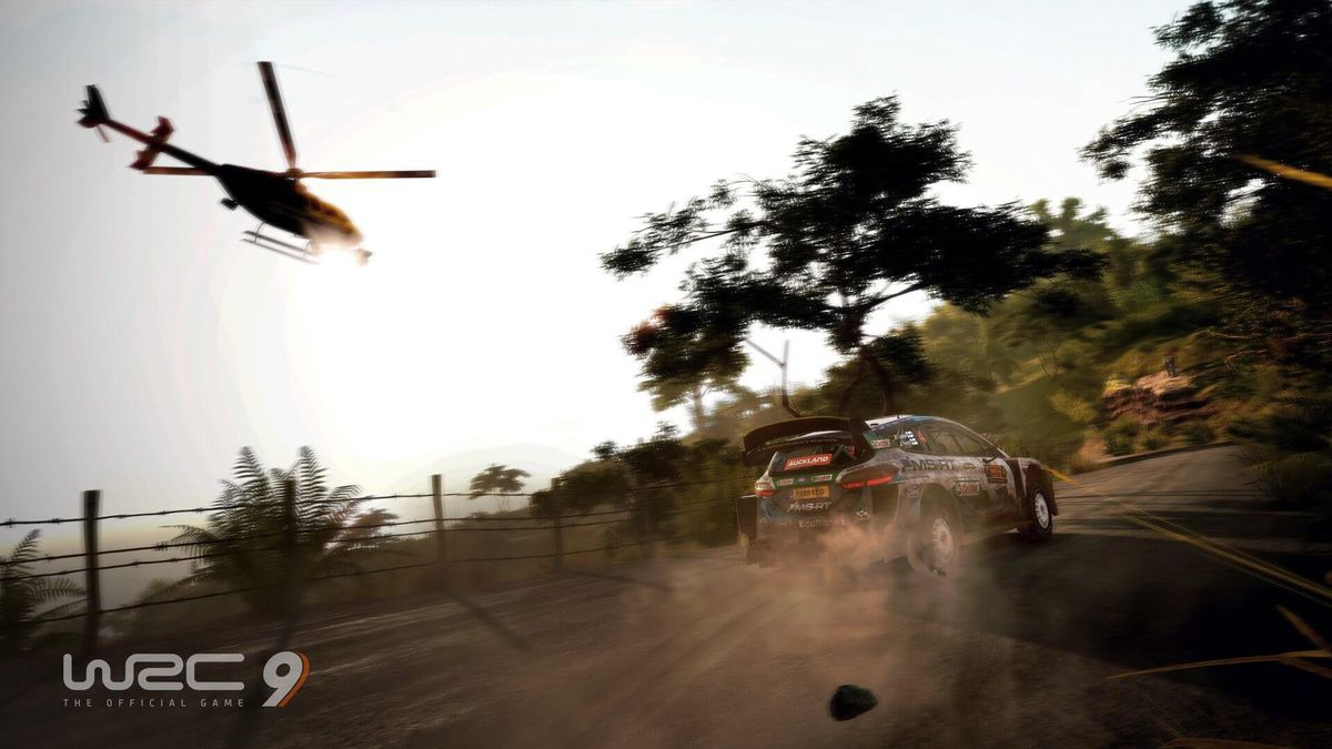 A helicopter, filming the race, chases a rally car sliding through a dirt road turn