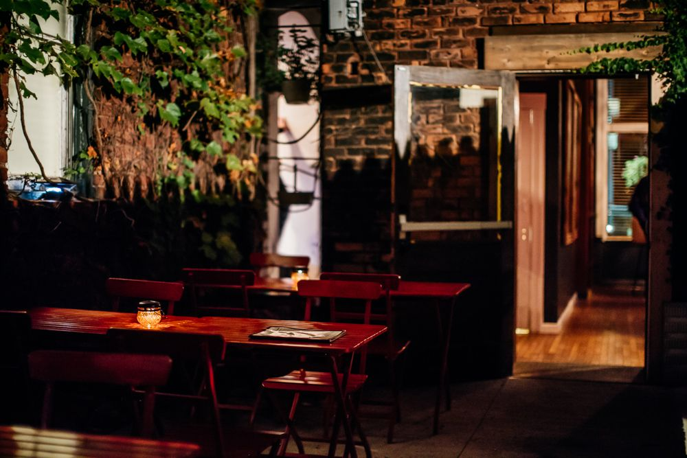 An nighttime scene of an outdoor patio at Mudgie's with tea candles on the tables.