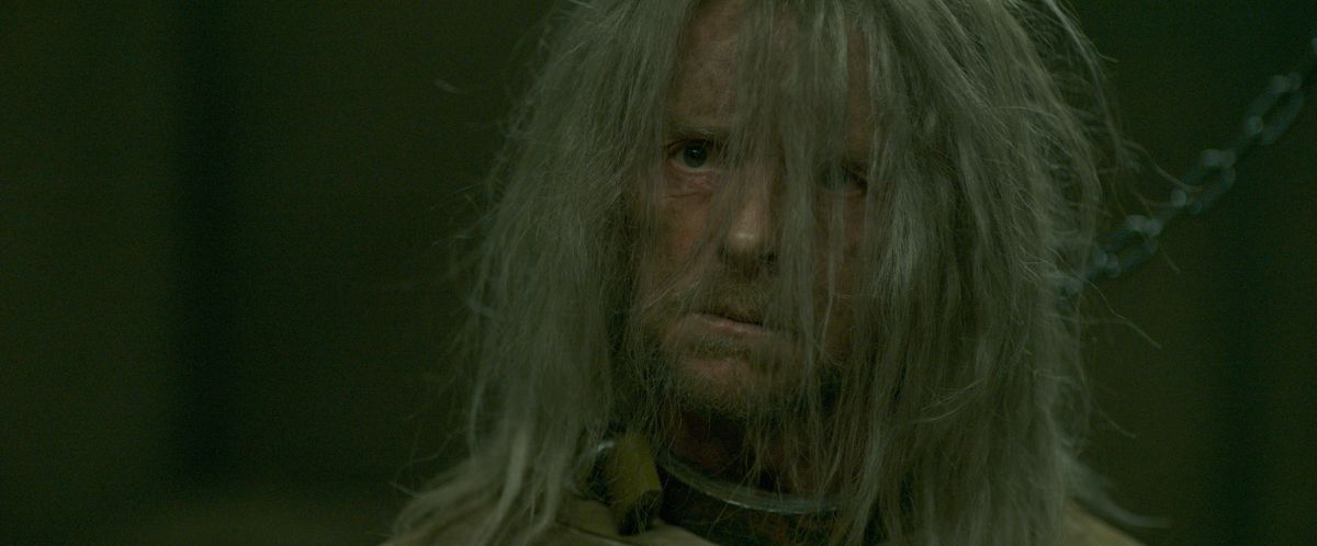Simon Pegg, wearing a dull metal collar that's chained to the wall, peers out from under a fringe of lank, ragged, long grey hair in Inheritance.