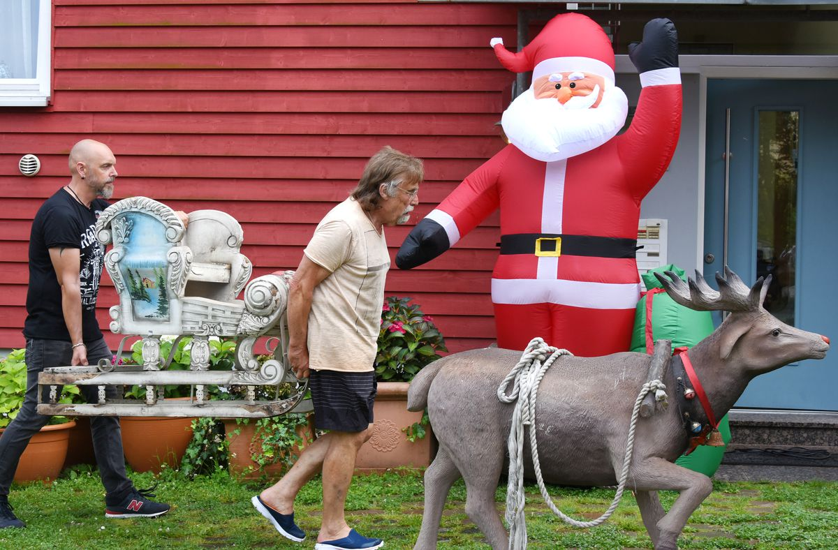 Two people carry a decorative sled in front of a house, past an inflatable Santa, and behind a statue of a reindeer.