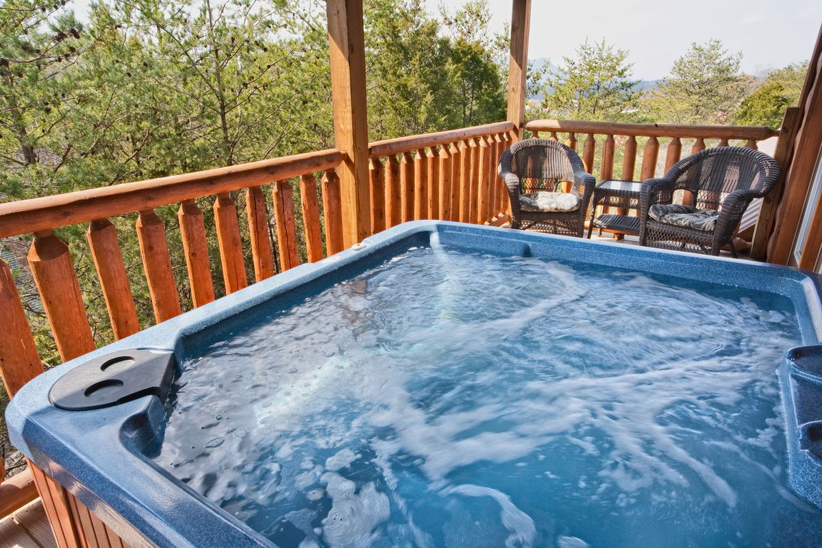 Hot tub on the balcony of a log cabin.