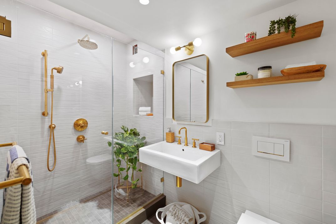 A bathroom with beige tiles and wooden shelves.