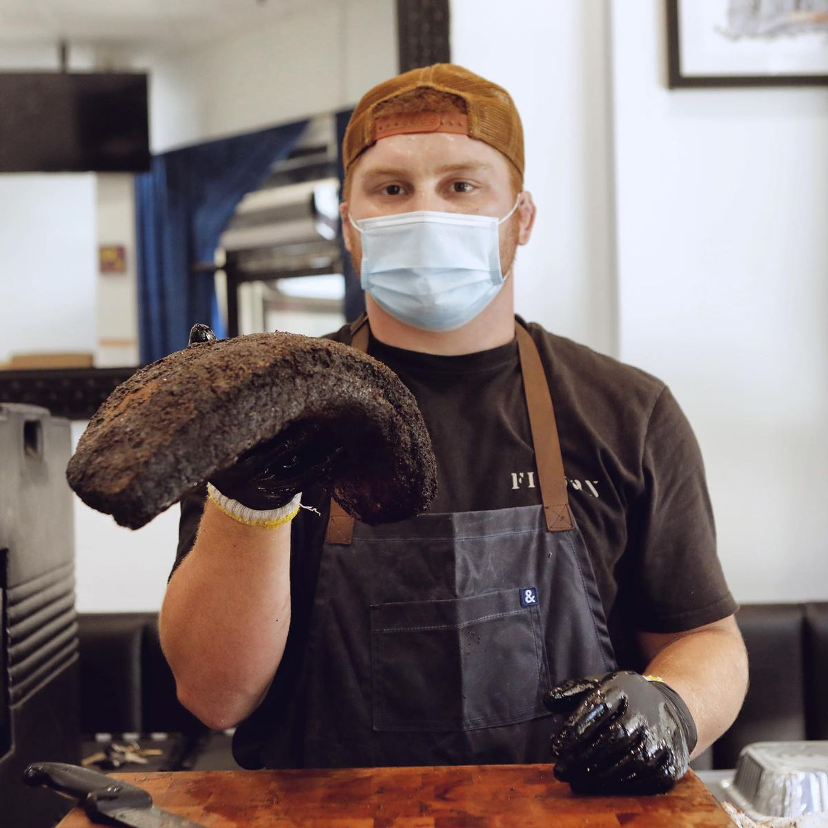 A man in a mask shows off a brisket in one hand, just off the pit.