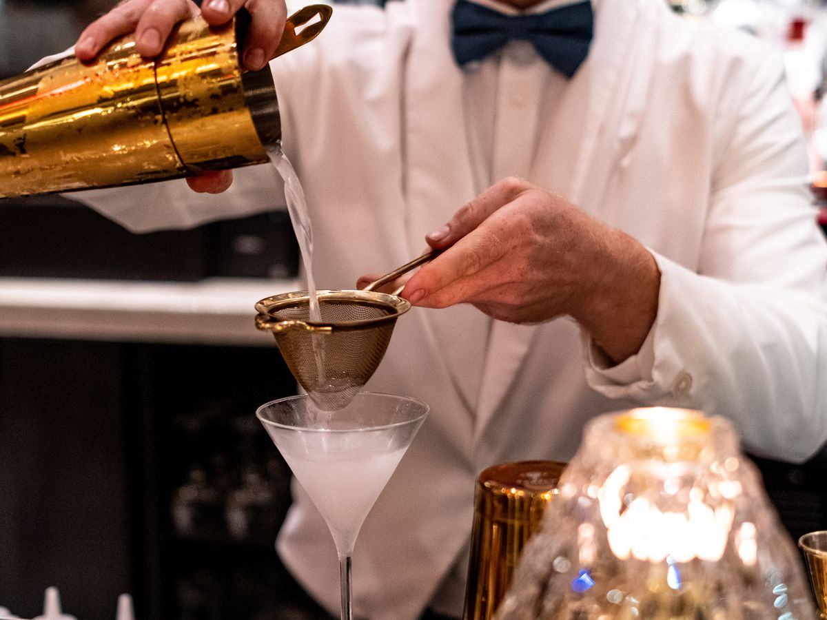 A bartender clad in a white coat and black bowtie pours a martini through a strainer into a glass