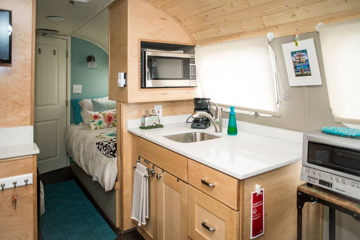 The inside of a trailer. There's cabinets with a counter and sink and a microwave above built into the right wall, and an opening ahead leads to a room with a small bed and light blue walls.