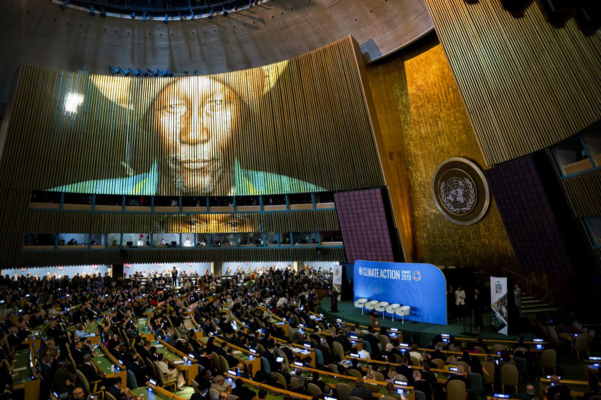 The General Assembly Hall during the UN Climate Action Summit showing a man's face on the huge video screen.