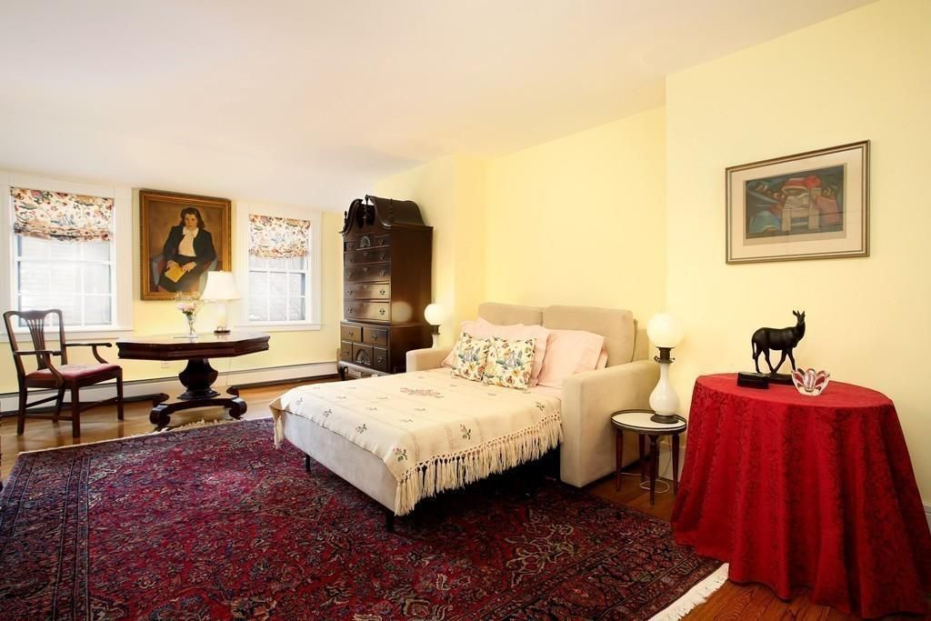 A bedroom with a bed, a table and chairs, and two windows.