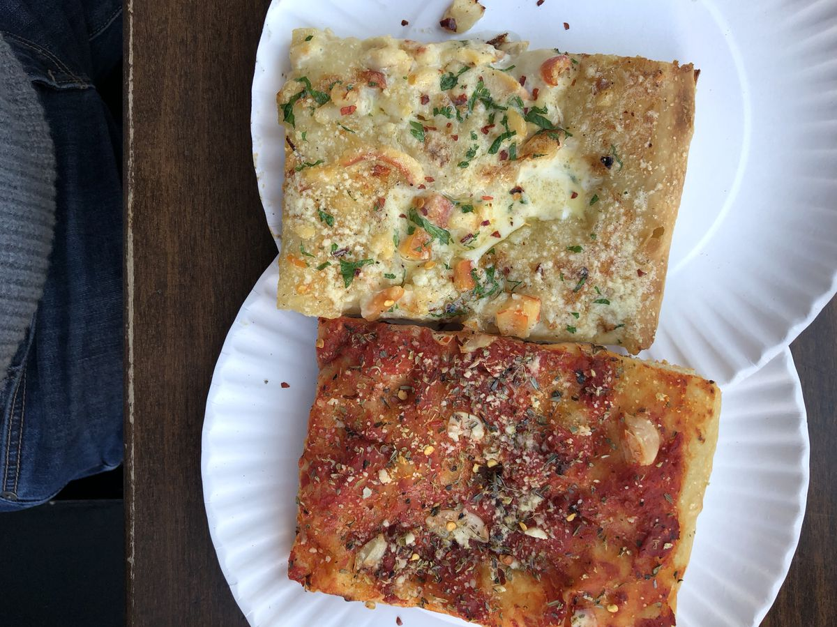 A white clam slice and a red tomato slice sit on paper plates at Gotham West Market
