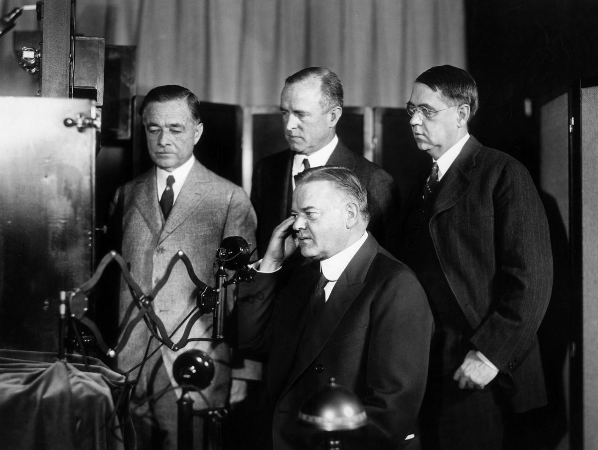 President Herbert Hoover participates in a demo of an early one-way video calling machine, which broadcast a television image along with a phone call.