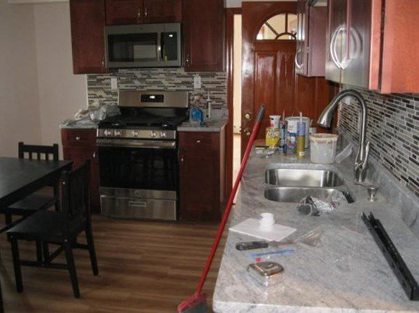 A view of a kitchen down the counter and toward the stove and oven, and there's a table and chairs.