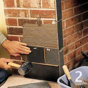 <p>Use a rubber mallet to firmly set the slate into the mortar. Thin cardboard strips act as tile spacers.</p>
