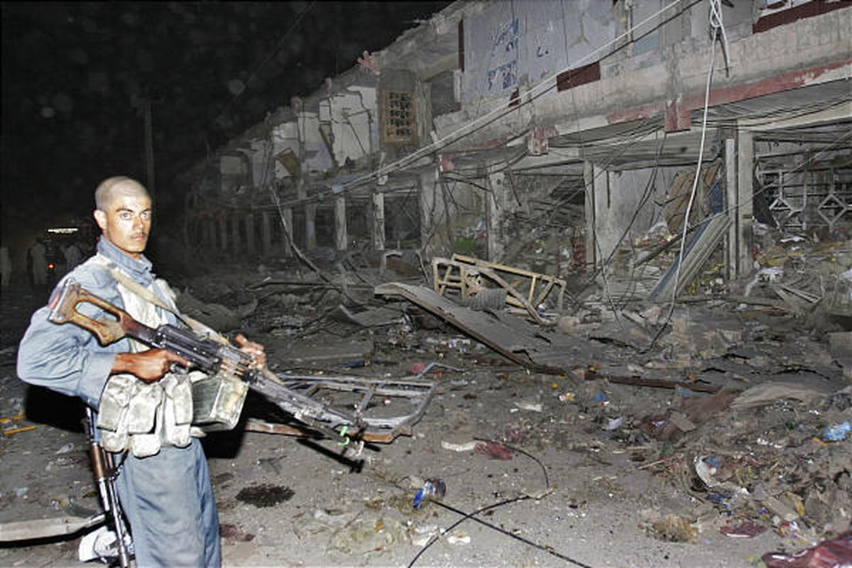 A policeman stands at the site after five car bombs detonated simultaneously in the southern Afghanistan city of Kandahar on Tuesday.