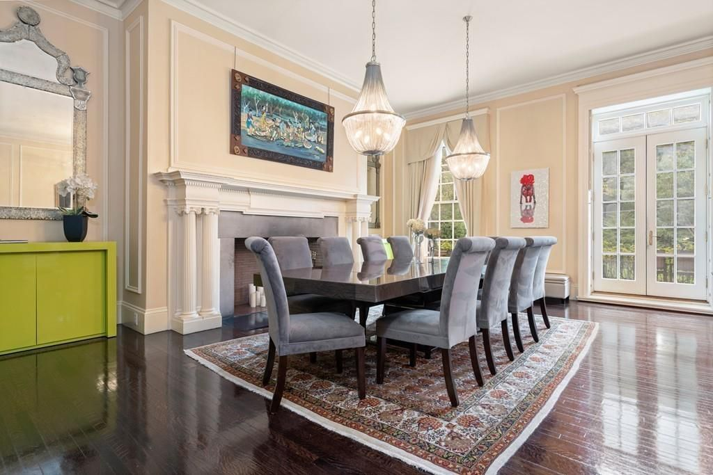 A large dining room with a table and chairs as well as a fireplace.