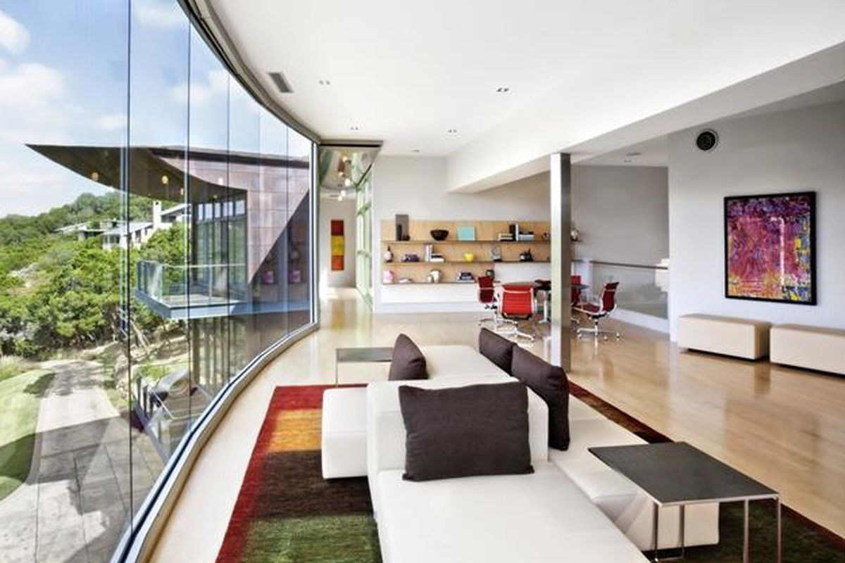 Sweeping contemporary with huge, curved glass wall overlooking landscape