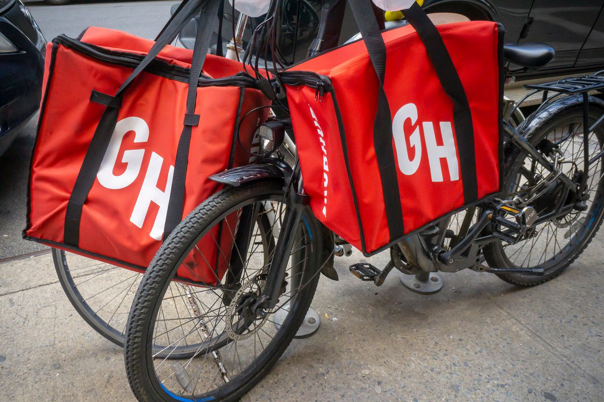A pair of delivery bikes with GrubHug bags slung over the handles