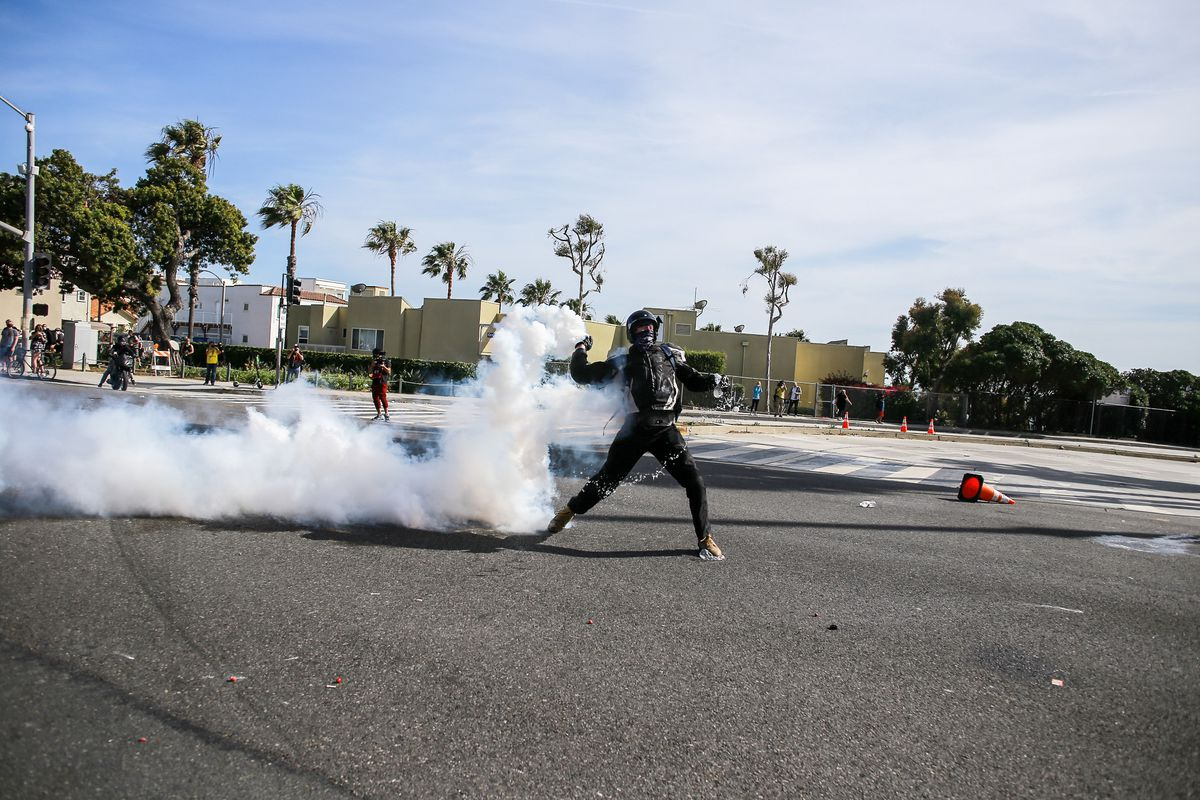 A protester return throws tear gas towards the police who...