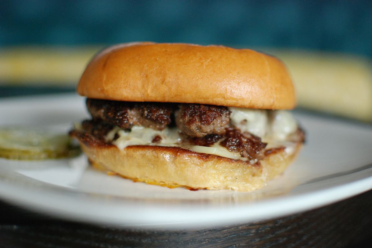 A skinny burger on a buttery bun with white cheese